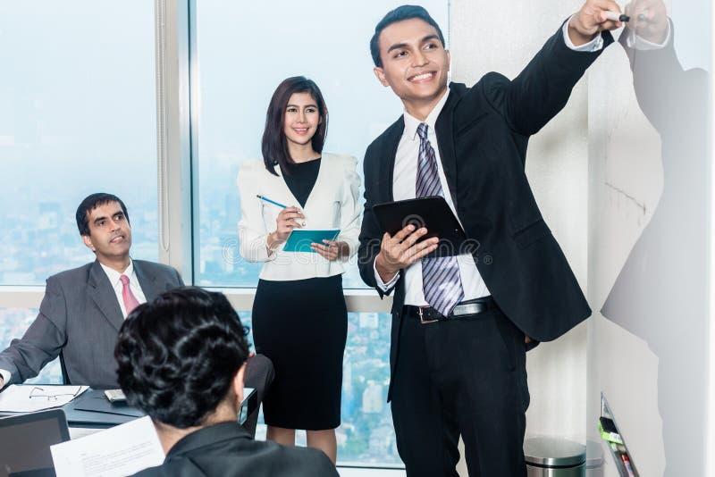 Empresarios en la reunión que escuchan la presentación foto de archivo