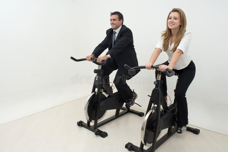 Empresarios en las bicis de ejercicio - horizontales imagenes de archivo