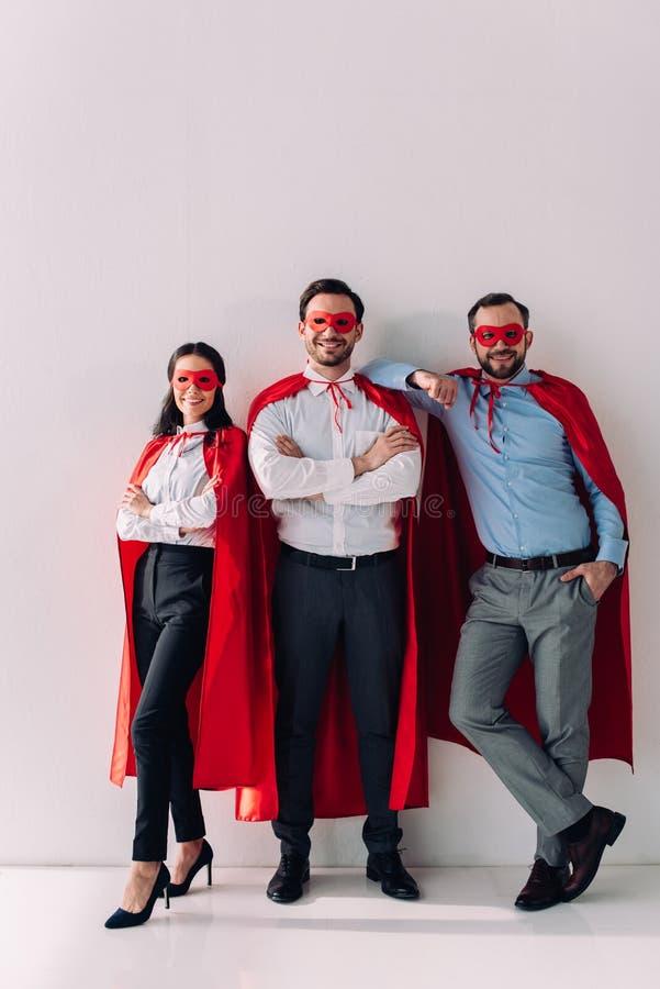 empresarios estupendos sonrientes en máscaras y cabos que miran la cámara fotos de archivo libres de regalías