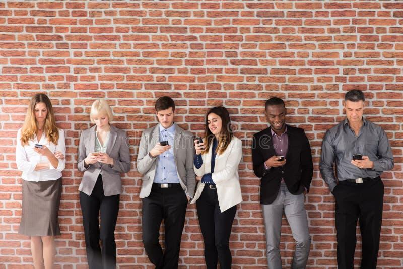 Empresarios felices que usan el teléfono elegante foto de archivo