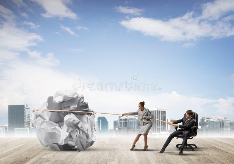 Empresarios haciendo un esfuerzo con una gran bola de papel ruinosa como signo de creatividad imagenes de archivo