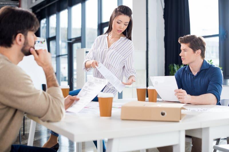 Empresarios jovenes profesionales que beben el café de las tazas de papel y que discuten los papeles imagenes de archivo