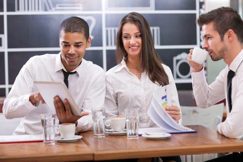 Empresarios jovenes que tienen una reunión de negocios en la mesa de centro fotos de archivo libres de regalías