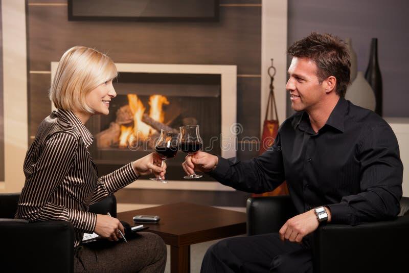 Empresarios jovenes que tintinean los vidrios de vino fotografía de archivo libre de regalías