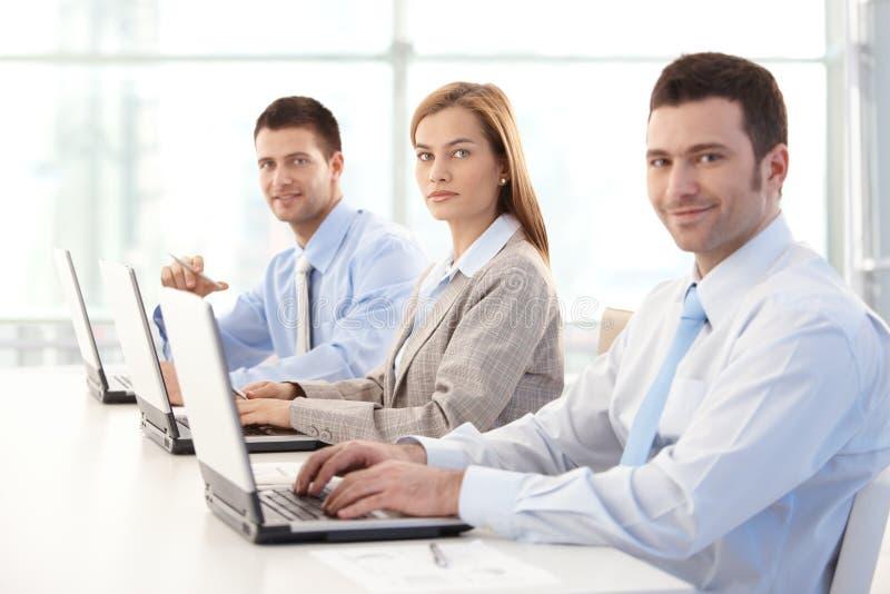 Empresarios jovenes que trabajan en la sonrisa de la computadora portátil imagen de archivo