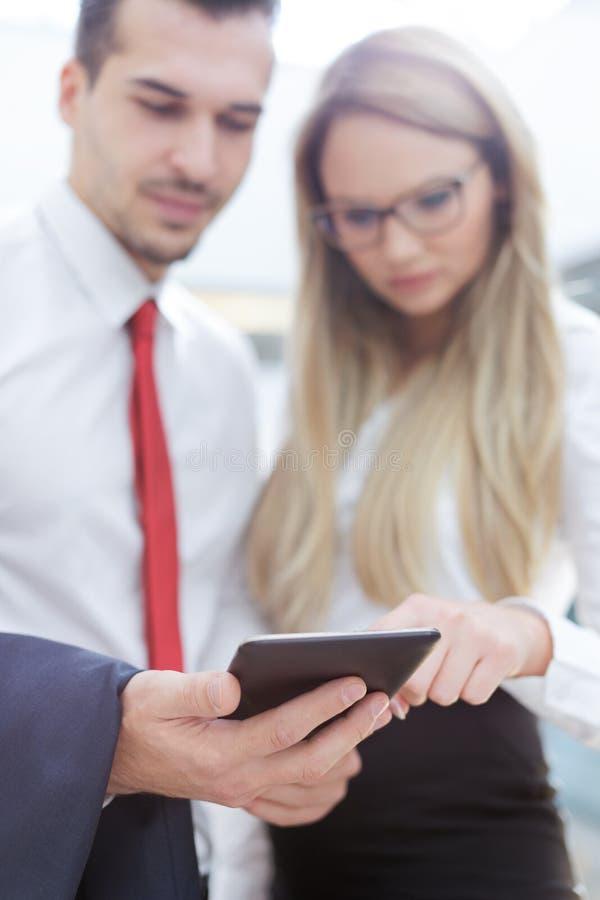 Empresarios jovenes que usan la tableta en centro de negocios imagen de archivo libre de regalías