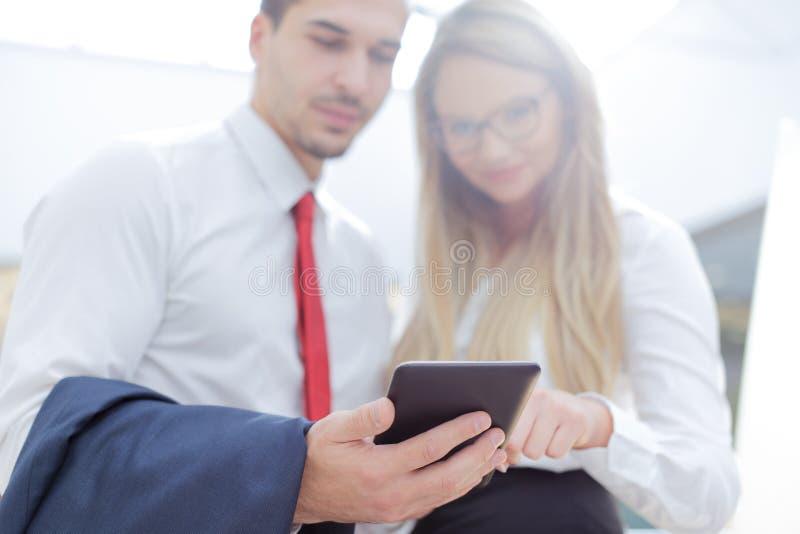 Empresarios jovenes que usan la tableta en centro de negocios imágenes de archivo libres de regalías
