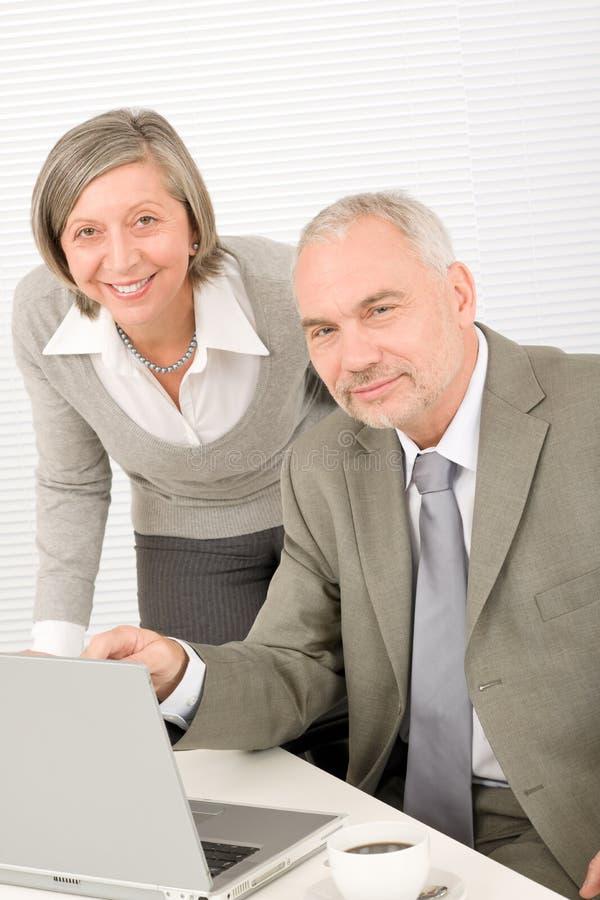 Empresarios mayores en trabajo de oficina sobre el ordenador fotos de archivo