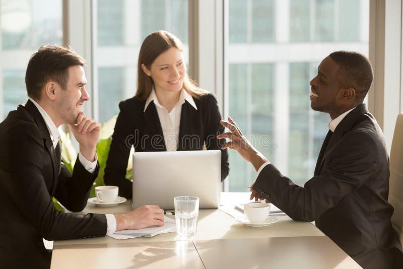 Empresarios multirraciales atractivos que hablan y que bromean, teniendo foto de archivo