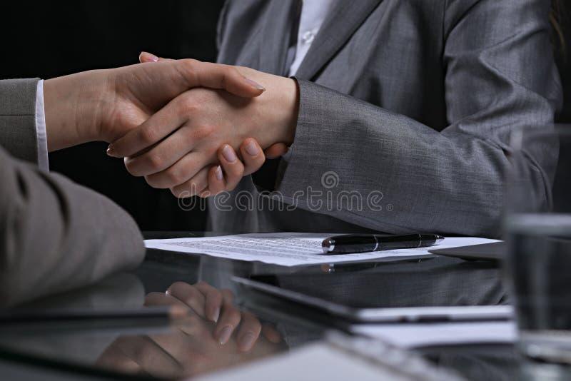 Empresarios o abogados que sacuden las manos en el encuentro sin fin Iluminación oscura imágenes de archivo libres de regalías