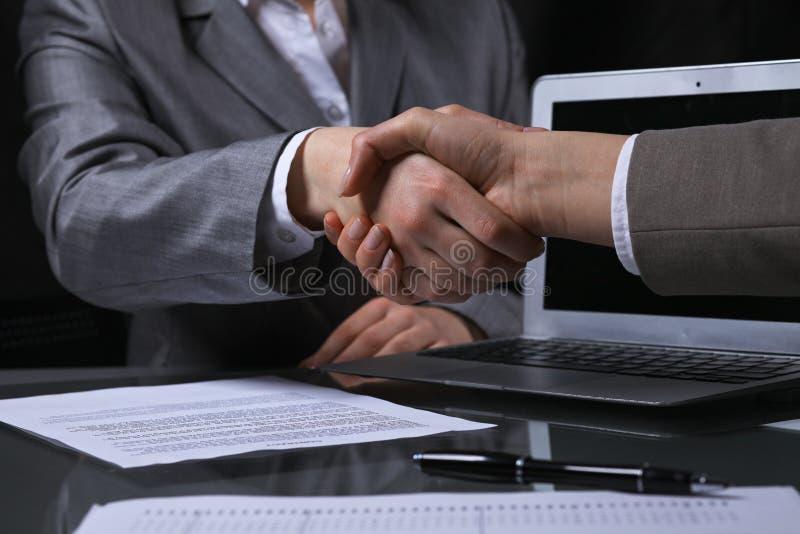 Empresarios o abogados que sacuden las manos en el encuentro sin fin Iluminación oscura foto de archivo