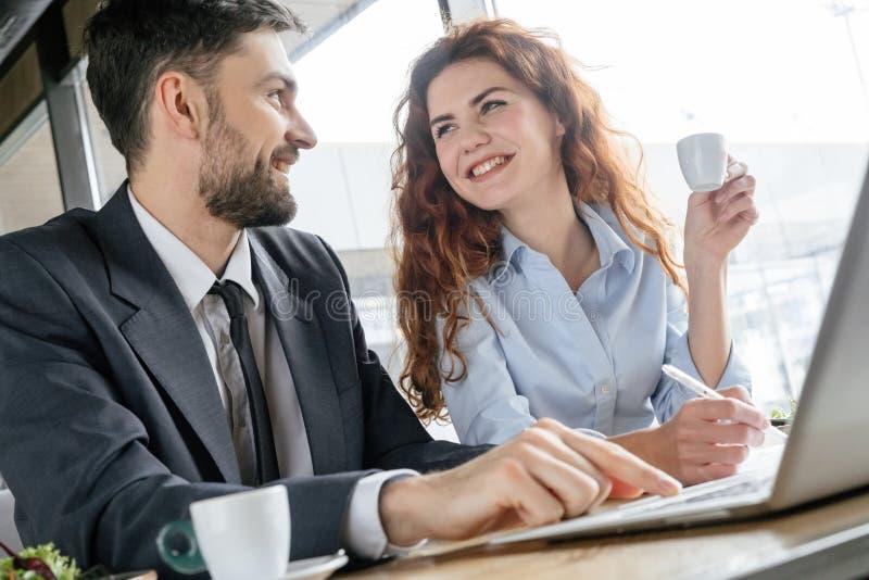 Empresarios que almuerzan almuerzo de negocios en el hombre que se sienta del restaurante que mecanografía en el ordenador portát fotografía de archivo