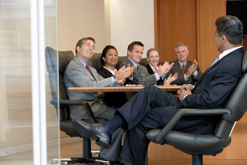 Empresarios que aplauden Boss In Meeting fotos de archivo