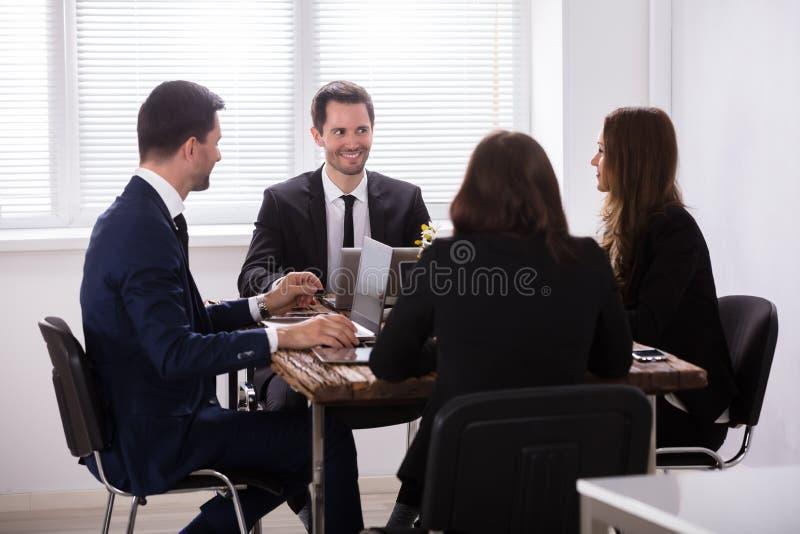 Empresarios que assisten a la reunión en oficina fotos de archivo