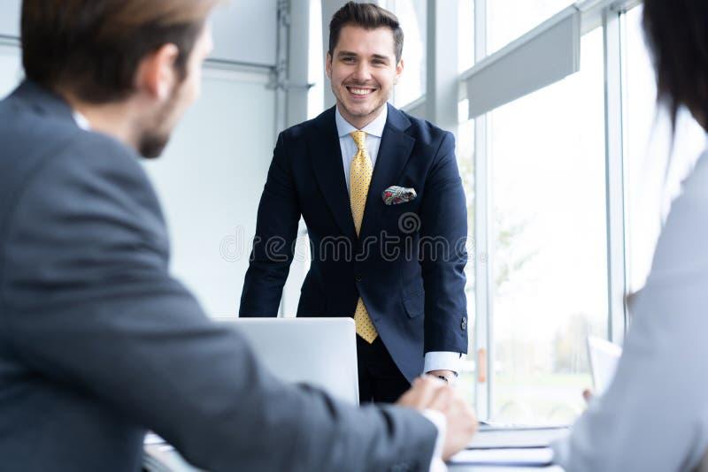 Empresarios que discuten junto en la sala de conferencias durante la reuni?n en la oficina foto de archivo
