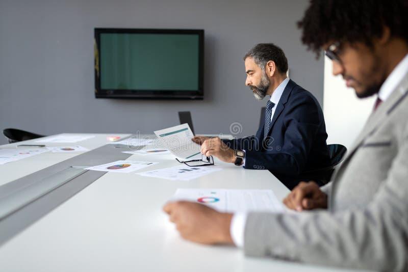 Empresarios que discuten junto en la sala de conferencias durante la reuni?n en la oficina imágenes de archivo libres de regalías