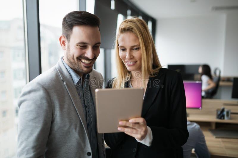 Empresarios que discuten mientras que usa la tableta digital en oficina fotografía de archivo