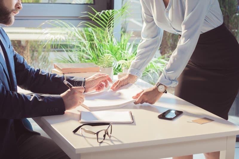 Empresarios que firman documentos durante la reunión imágenes de archivo libres de regalías