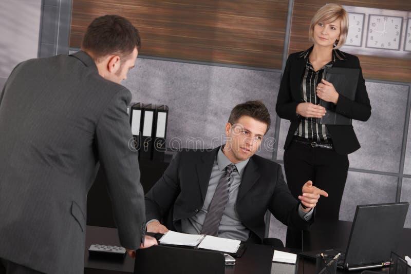 Empresarios que hablan en oficina foto de archivo