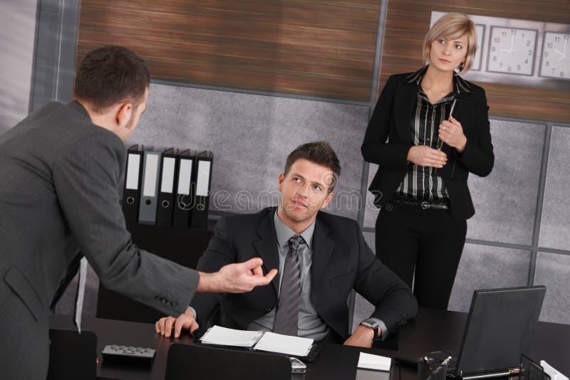 Empresarios que hablan en oficina imagen de archivo