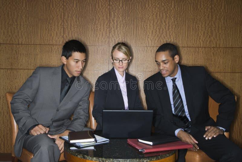 Empresarios que miran la computadora portátil foto de archivo