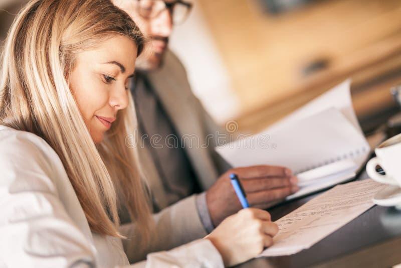 Empresarios que planean y que trabajan en el documento importante imagenes de archivo