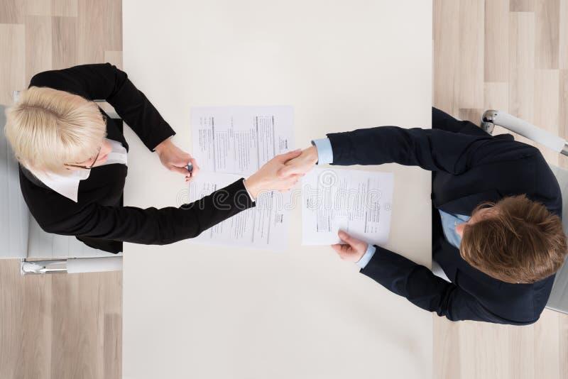 Empresarios que sacuden la mano en el escritorio fotos de archivo