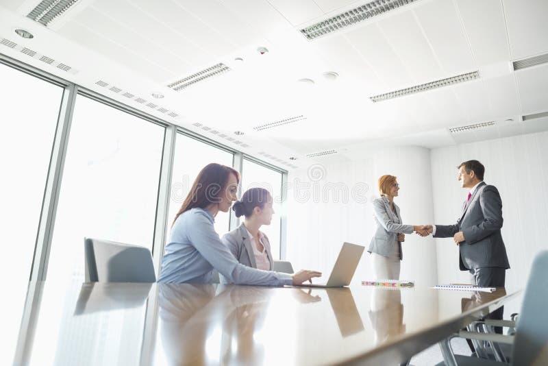 Empresarios que sacuden las manos en sala de juntas fotos de archivo
