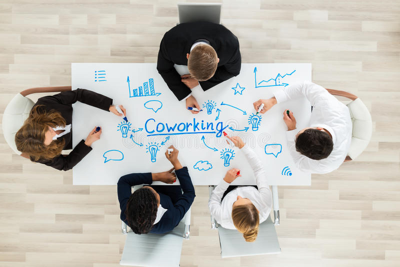 Empresarios que se sientan en el espacio de CoWorking imágenes de archivo libres de regalías