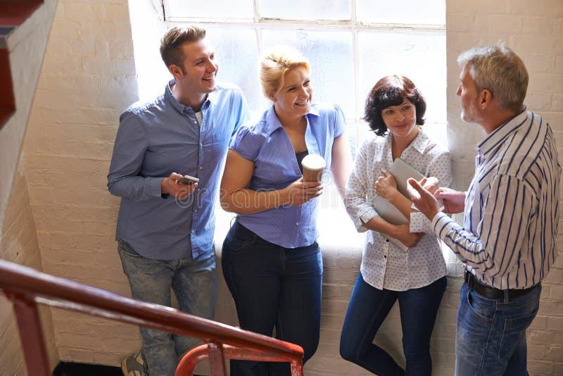 Empresarios que tienen reunión informal sobre las escaleras de la oficina imagen de archivo