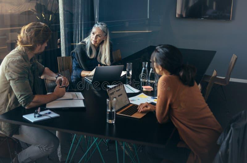 Empresarios que tienen una reunión en oficina foto de archivo