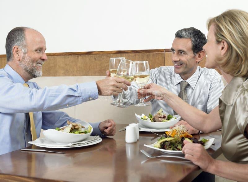 Empresarios que tuestan bebidas imagen de archivo