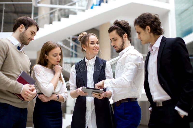 Empresarios que usan la tableta digital junto en oficina fotografía de archivo