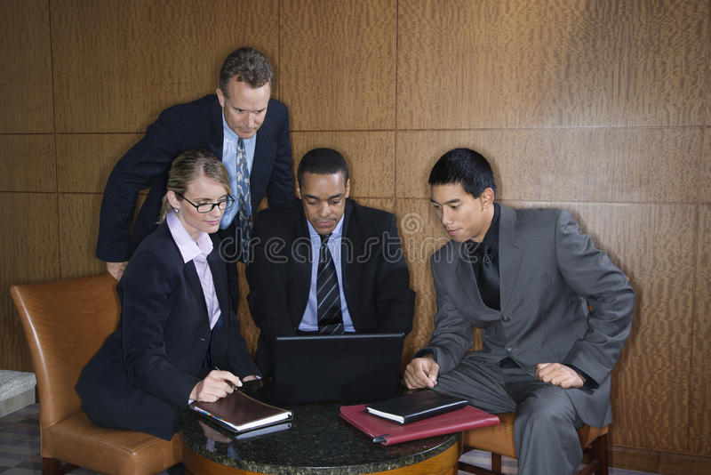 Empresarios recolectados alrededor de una computadora portátil fotos de archivo libres de regalías