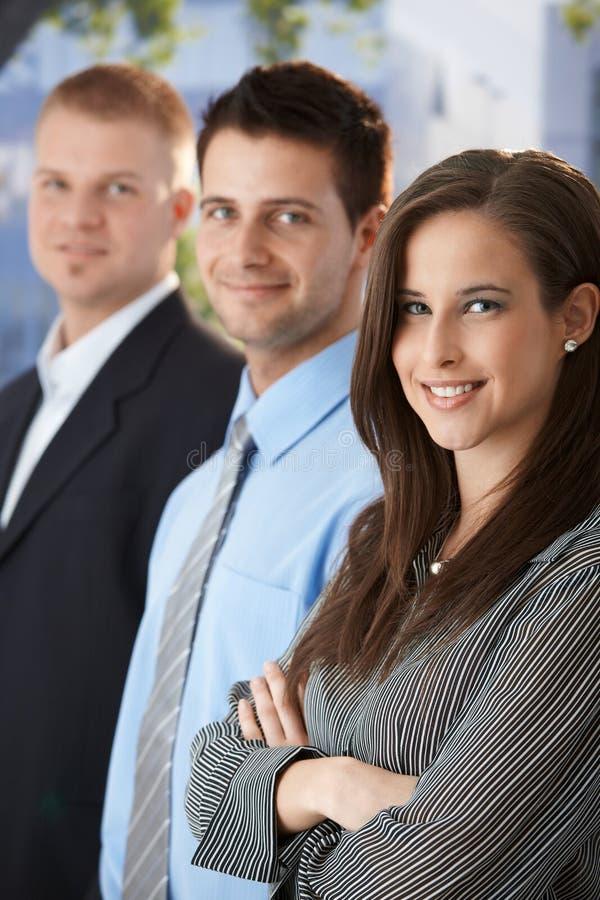 Empresarios sonrientes que se colocan al aire libre fotos de archivo