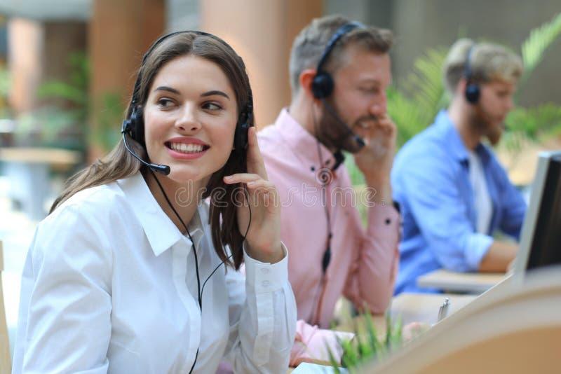 Empresarios y colegas jovenes positivos atractivos en una oficina del centro de atención telefónica fotos de archivo libres de regalías