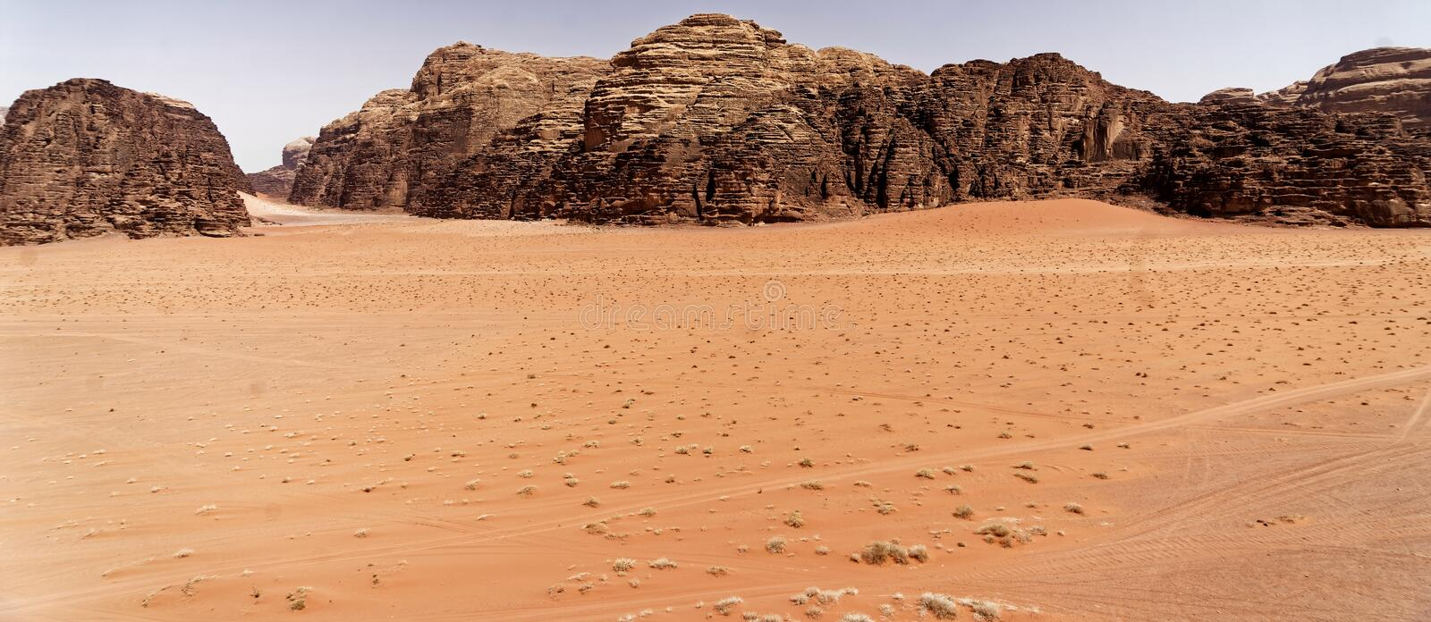 The emptiness of the great desert in the nature reserve of Wadi Rum, with large mountains of red sandstone in the background and t royalty free stock photo