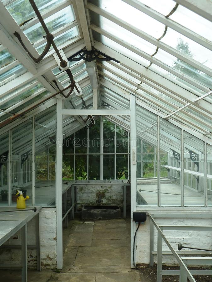 Empty abandoned vintage glass greenhouse. An empty abandoned vintage glass and brick greenhouse with old metalwork on the windows royalty free stock images
