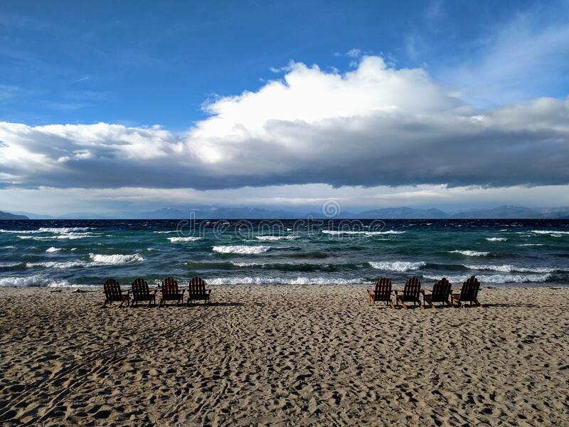 Empty Adirondack chairs along the shoreline of Lake Tahoe from the Nevada side on a windy fall day, choppy water. Full white clouds against a blue sky with royalty free stock images