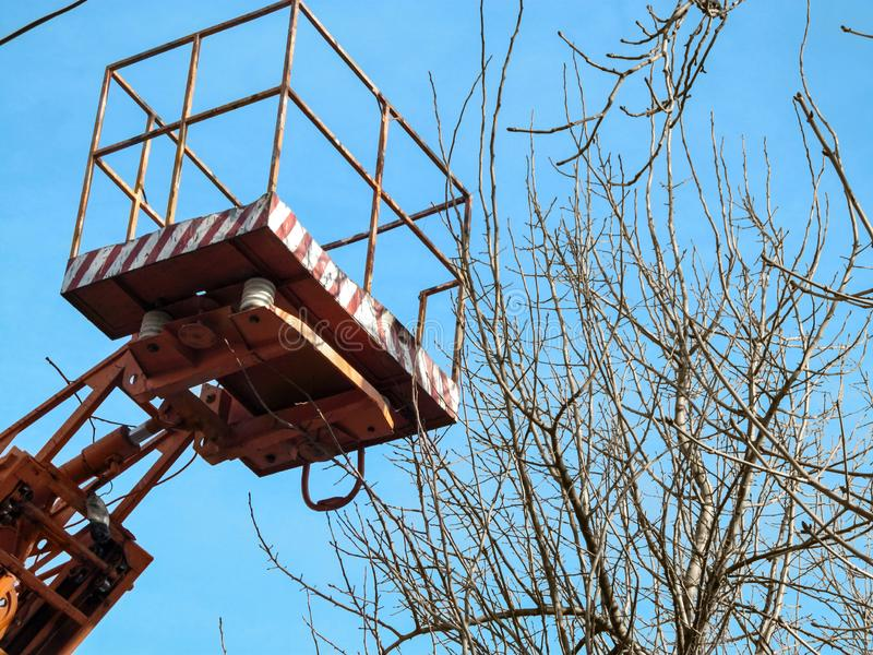 Empty aerial work platform in the air against the blue sky and bare tree branches, close-up. The concept of work on the spring. Pruning of trees using a bucket stock photos