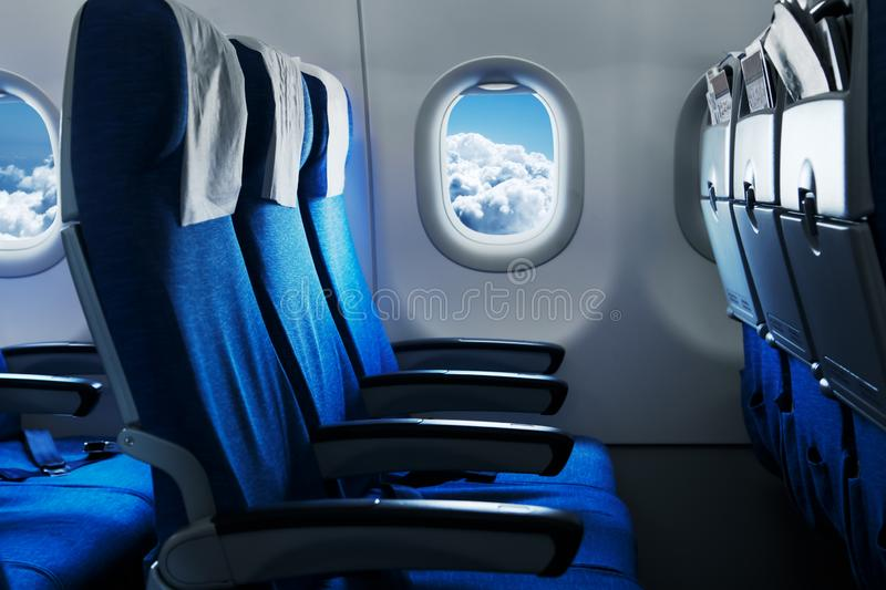 Empty air plane seats. Airplane interior. Empty air plane seats. Blue sky and clouds in the window. Airplane interior stock images
