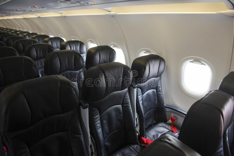 Empty aircraft black leather economy class seats and windows stock image