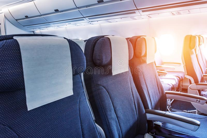 Empty aircraft seats and light shine porthole windows royalty free stock photo