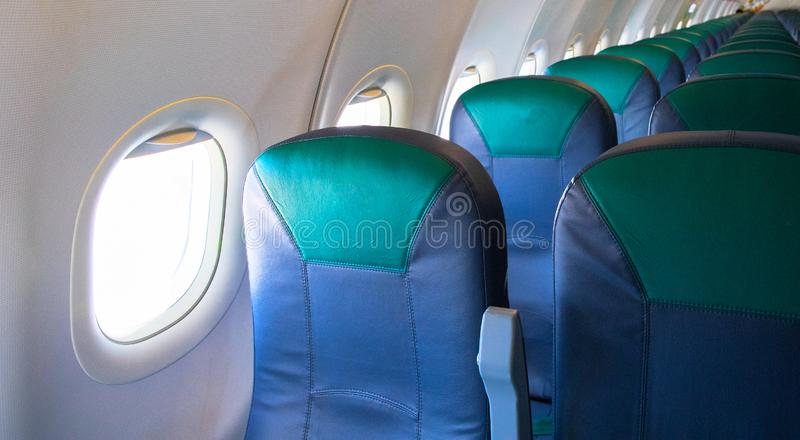 Empty airplane chairs and sunlight in illuminator. Aircraft interior photo. Empty plane waiting for passengers to load stock photography