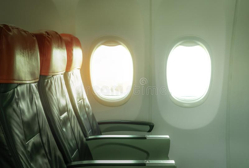 Empty airplane seat economy class in the cabin of the commercial airline. Cheap plane seat with windows and sunlight. Passenger royalty free stock photography