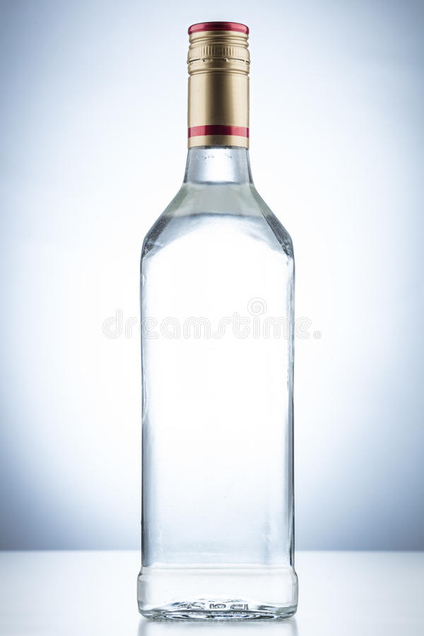Empty alcohol glass bottle. With no label and a gold and red cap on a white background royalty free stock image
