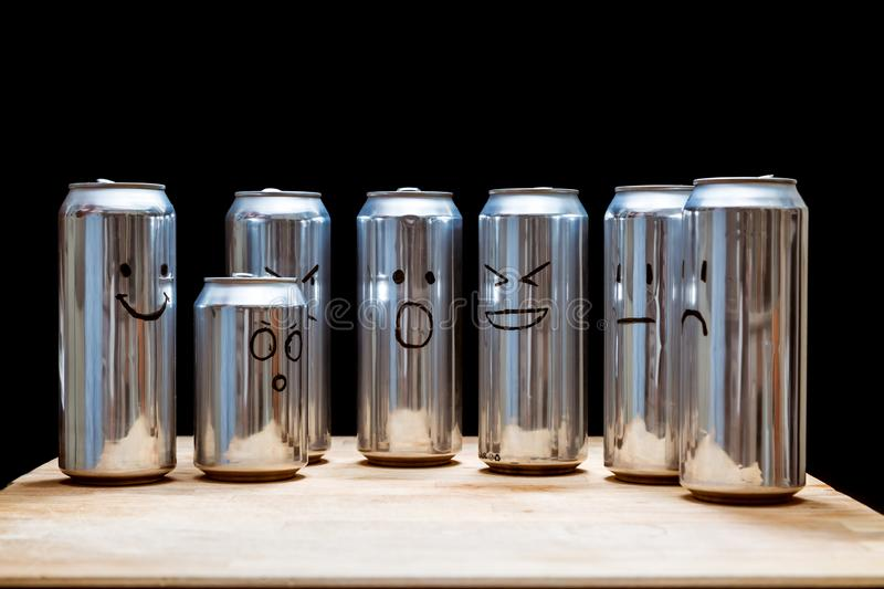 Empty aluminum cans as a human society. Instead faces smilies drawn on the trash. Emoji smile angry surprised disappointed sad stock photography
