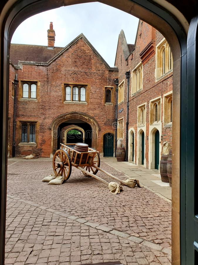 Empty ancient courtyard at Henry 8th& x27;s Hampton Court Palace framed by arched doorway and highlighting a cart stock images