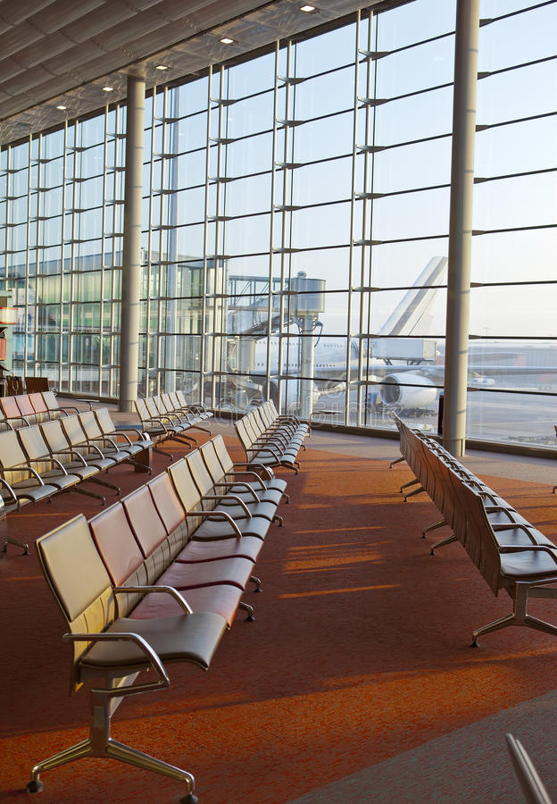 Empty armchairs in hall of expectation of airport and plane behind window royalty free stock photos