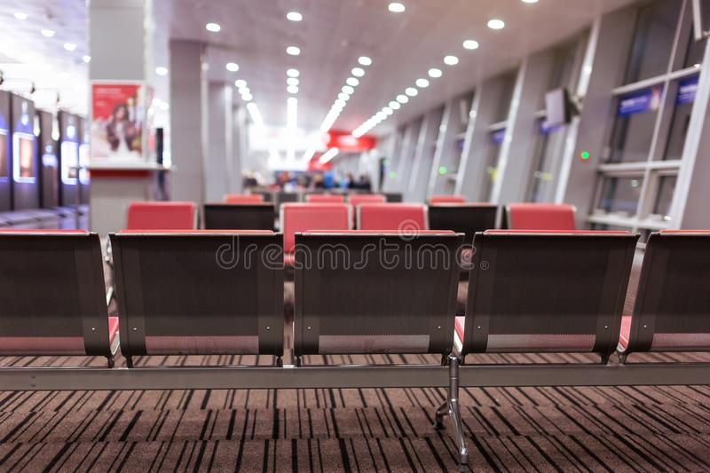 Empty armchairs in hall of expectation of airport and plane behind window.  stock images